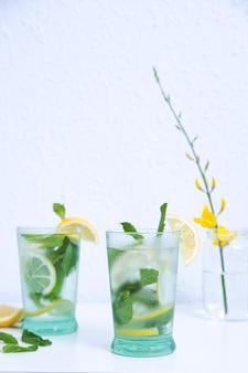 Colpo verticale di due bicchieri di limonata fredda con menta e limoni isolati su una parete bianca