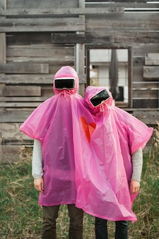 Vertical shot of two people in vr headsets sharing a pink plastic raincoat