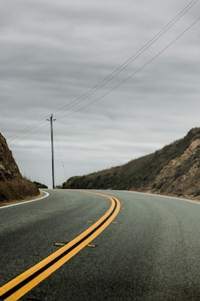 Vertical shot of a two-sided highway surrounded by hills with the cloudy grey sky in the