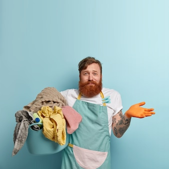 Vertical shot of unaware clueless red haired man cannot choose detergent for washing laundry