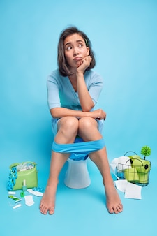 Vertical shot of unhappy thoughtful woman looks away sits on toilet bowl suffers from constipation spends much time in lavatory wears lace blue panties has frustrated expression while peeing