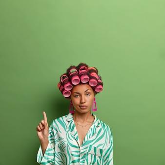Colpo verticale di donna dalla pelle scura indifferente indossa bigodini e indica sullo spazio della copia, mostra uno spazio vuoto contro il muro verde per il tuo promo, si preoccupa dell'aspetto, si prepara per la data