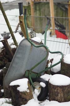 Vertical shot of an upside-down wheelbarrow during winter