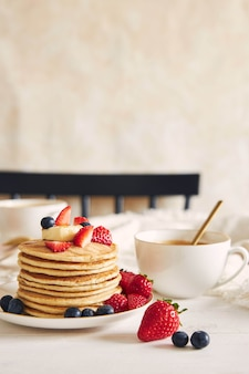 Vertical shot of vegan pancakes with colorful fruits ner a coffee and syrup