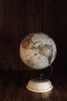 Vertical shot of a vintage globe model on a wooden table with a wooden wall in the background