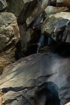 Colpo verticale dell'acqua che scorre giù attraverso le rocce in vietnam