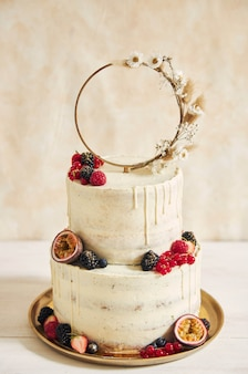 Vertical shot of a wedding cake decorated with fresh fruits and berries and a flower ring