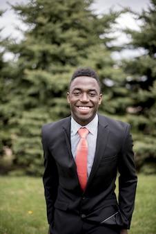 Colpo verticale di un maschio ben vestito mentre sorride Foto Gratuite
