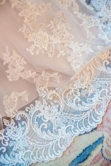 Colpo verticale di un tessuto di pizzo da sposa bianco