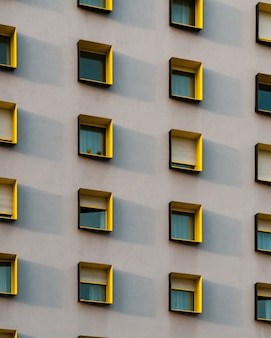 Vertical shot of a white building with black and yellow window frames