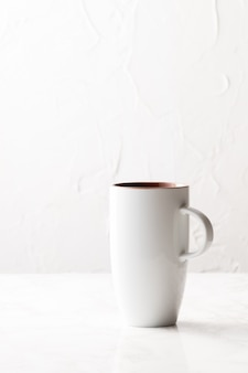Vertical shot of a white ceramic cup on a white surface