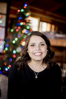 Colpo verticale di una femmina bianca che sorride davanti ad un allegro festivo