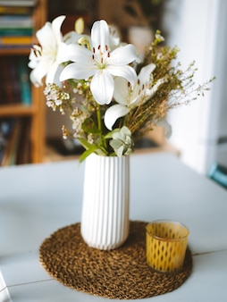 Vertical shot of white orchids in a vase on a table inside a room in madeira, portugal