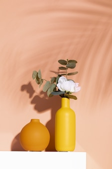 Vertical shot of a white rose in a decorative yellow vase against an orange wall
