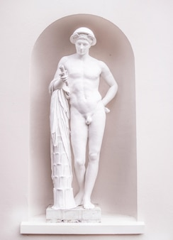 Vertical shot of a white stone sculpture of a naked male