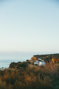 Vertical shot of a white van near a cliff by the sea during daytime