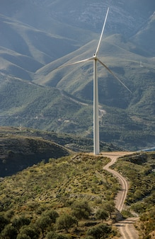 Vertical shot of a white wind fan standing on a green field behind the mountains