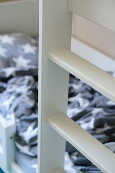 Vertical shot of a white wooden ladder near the bed