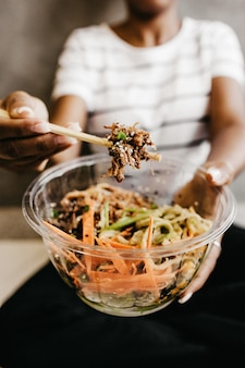 Vertical shot of a woman holding a clear plastic bowl with vegetable salad and chopsticks
