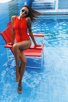 Vertical shot of woman in a red swimsuit and sunglasses, sitting lifeguard chair at swimming pool area.