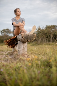 Vertical shot of a woman sitting on a piece of wood in the field