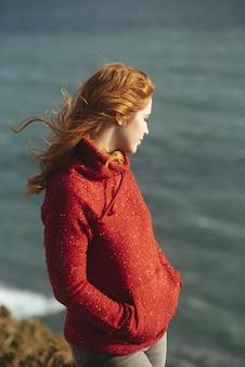 Colpo verticale di una donna in piedi sulla riva con il mare
