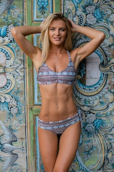 Vertical shot of a woman in swimsuit behind a multicolored wall with different patterns