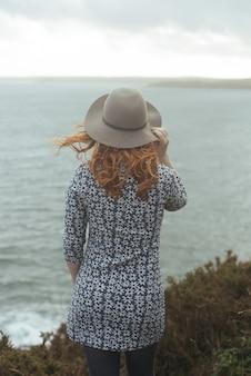 Colpo verticale di una donna che indossa un cappello con il mare