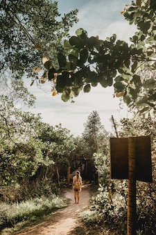 Vertical shot of a woman with a backpack walking on a forest path barefoot