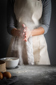 Vertical shot woman with flour in palms