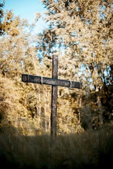 Colpo verticale di una croce di legno su un campo erboso