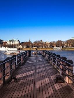 Vertical shot of a wooden dock leading to the river with the city
