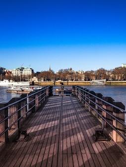 Colpo verticale di un pontile in legno che porta al fiume con la città