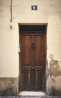 A vertical shot of a wooden door with the number 6 above it