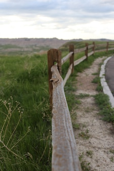 Vertical shot of a wooden fence in the middle of a road and a grass field
