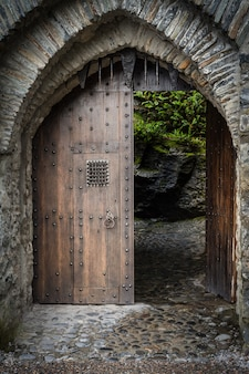 Vertical shot of the wooden gate at the entrance of a beautiful historical castle