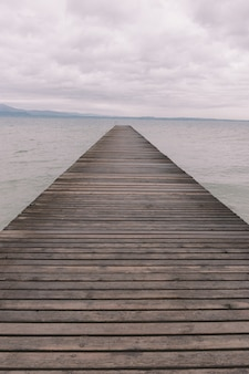 Vertical shot of a wooden pier over the calm ocean under the beautiful cloudy sky