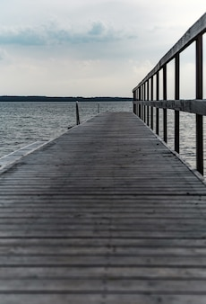 Vertical shot of a wooden pier at the cpast of the beautiful see under a cloudy sky