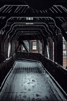 Vertical shot of a wooden road  leading to the train covered with snow