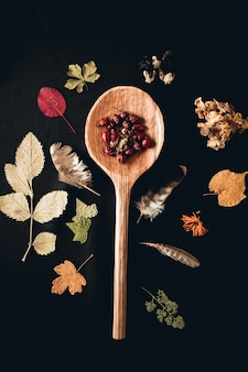 Vertical shot of a wooden spoon surrounded with different plants leaves and feathers