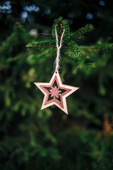 Vertical shot of a wooden star-shaped christmas ornament hanging from a pine tree