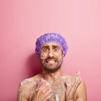 Colpo verticale di un uomo preoccupato che ha fretta durante la mattina, lava il corpo con gel e spugna, indossa un copricapo impermeabile, sta nudo in bagno, fa la doccia