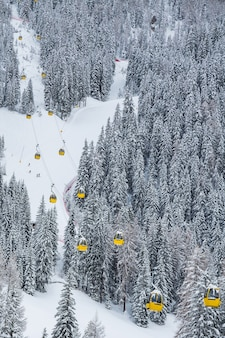 Vertical shot of yellow cable cars in the mountain during winter