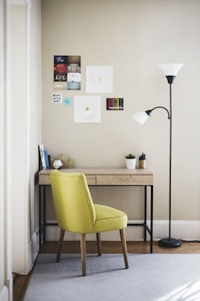 Vertical shot of a yellow chair and tall lamp near a wooden table with books and plant pots on it