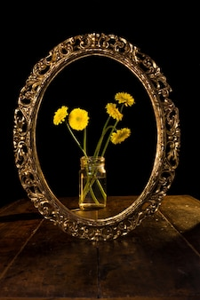 Vertical shot of yellow flowers in a glass jar reflected on the mirror