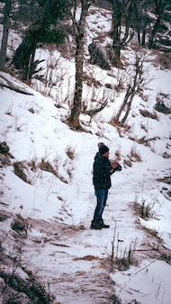 Vertical shot of a young asian man in a warm coat and hat taking photos in a winter park
