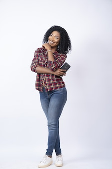 Vertical shot of a young black female holding her phone smiling