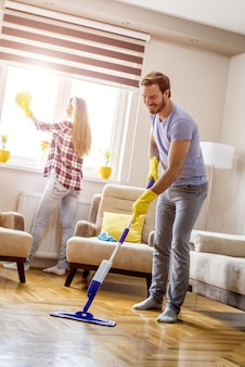 Vertical shot of a young caucasian couple cleaning home and having fun