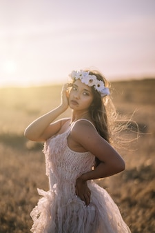 Vertical shot of a young caucasian female in white dress and white flower wreath posing in a field
