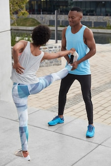 Vertical shot of young dark skinned woman has backache, raises legs, does stretching exercises together with coach, pose outside. togetherness, sport, training concept. black guy helps with workout